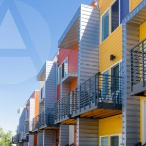 Bright coral and yellow apartment buildings with patios illustrate rental investment property.