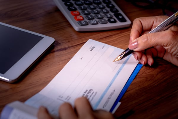 Woman-Writing-Checks-Checkbook-IRA