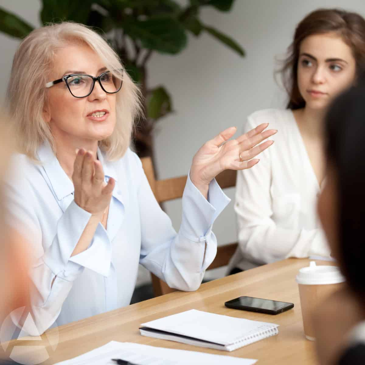 Savvy business woman sitting at a table with other women explaining retirement saving tips for women.