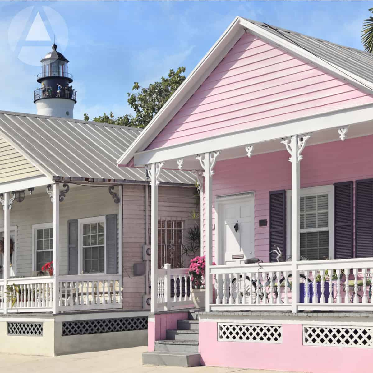 Colorful pink and grey cottages with white Key West-style trim and tin roofs, perfect rental property investments.